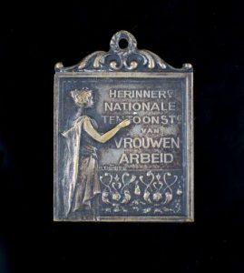 metalen hanger gemaakt naar aanleiding van de nationale tentoonstelling van vrouwenarbeid 1898
